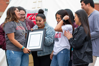 Native American students and staff hold a plaque as they gather on the WSU Pullman campus.