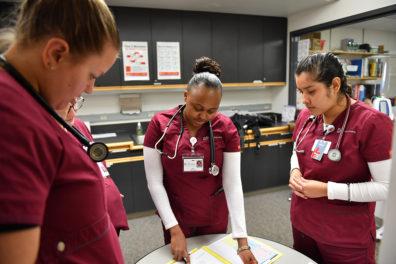 Nursing students talking around a table.