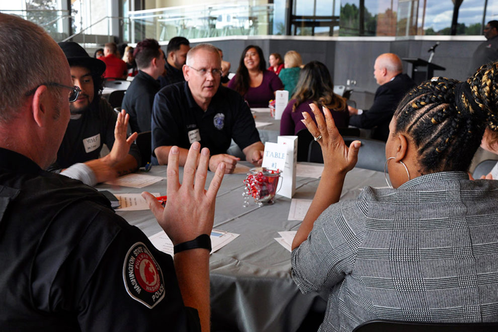 WSU police officers talk with students while seated at a table.
