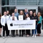group holding Apple Distinguished School banner