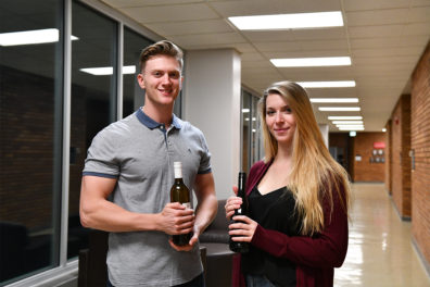Two students poise for a picture while holding bottles of wine.