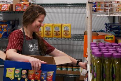 Ulyana Fisenko stocks shelves at the WSU Tri-Cities Cougar Cupboard.