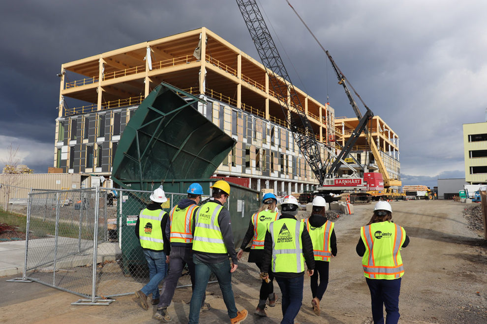 People with hard hats and safety vests walking through a construction site.