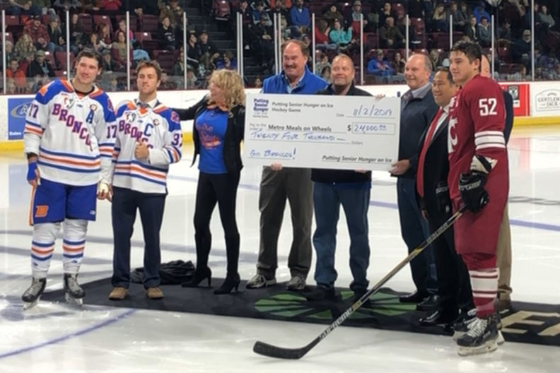 Hockey players present a donation on the ice rink.