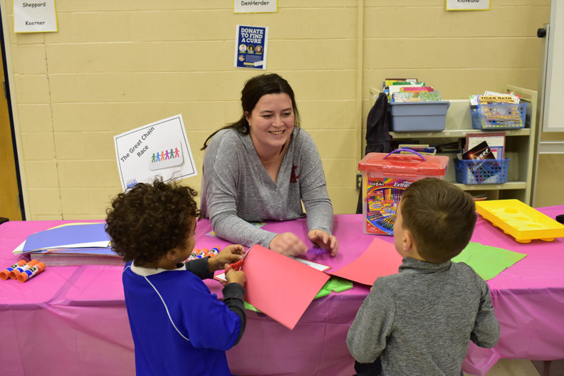 A College of Education student interacts with two young children.