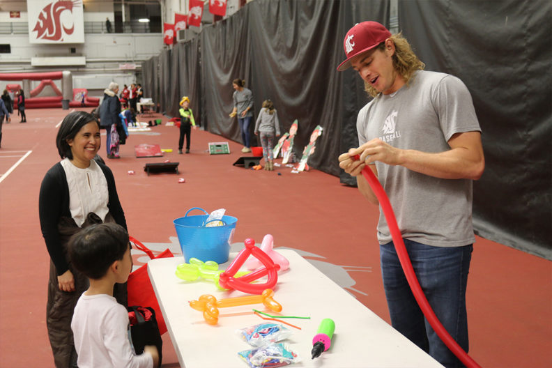 Radd Thomas, a pitcher for the Washington State baseball team, makes balloon animals for children at the annual Butch's Bash.