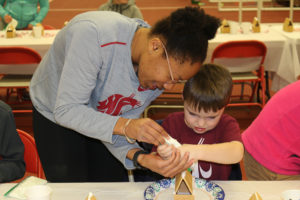 WSU student athletes helping children make gingerbread houses.