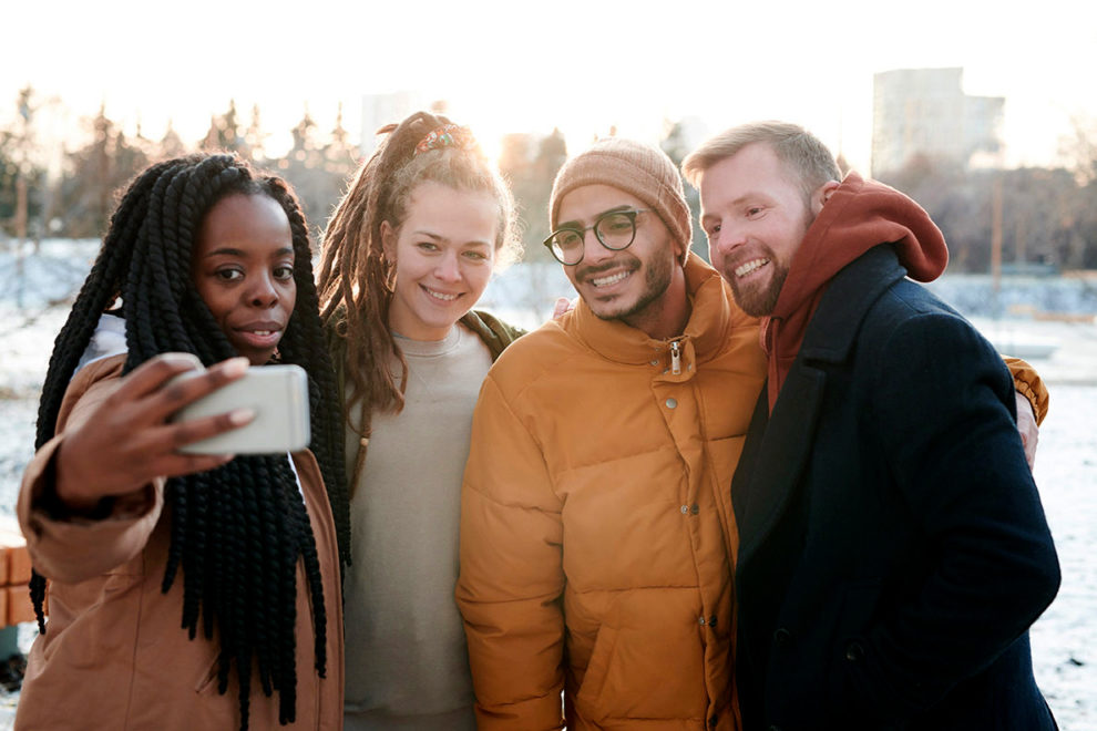 Four people taking a selfie.