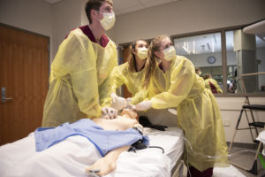Nursing BSN students practicing on a simulation mannequin.