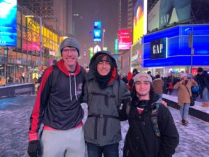 Bobby Belter, James Madamba, and Glen Bennett pose for a picture in NYC's Time Square.