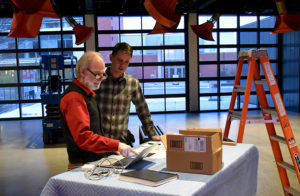 Trimpin (left) and a museum curator install Ambiente432 at the Jordan Schnitzer Museum of Art WSU.
