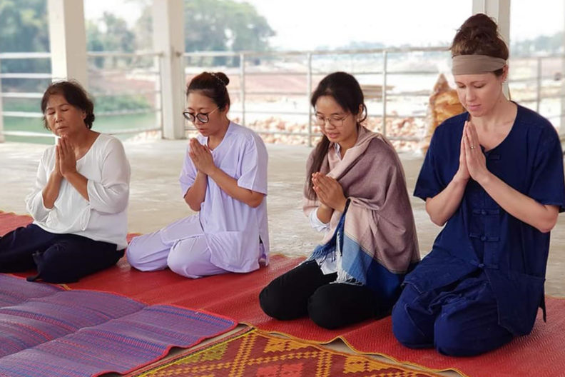 Four women practice guided meditation at a temple in Thailand.