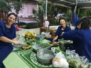 WSU College of Nursing PhD student Michelle Closner and Assistant Professor Andra Davis help prepare the evening meal with Sureeporn Thanasilp, of Thailand's Chulalongkorn University, at Arokhayasala Khampramong Temple in Sakon Nakhon, Thailand.