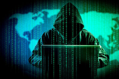 A hooded figure at a computer in front of a map with binary digits dropping down in front