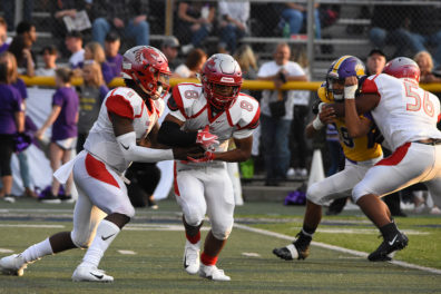 A football quarterback hands the ball off to a running back.