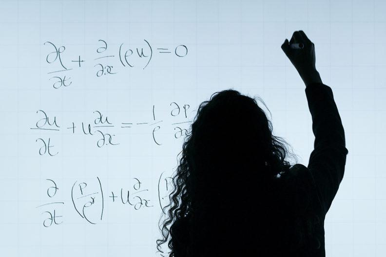 Female engineer writing equations.