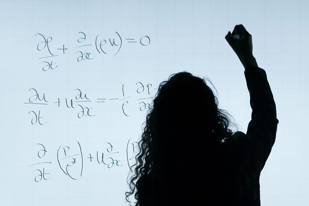 Female engineer writing equations.