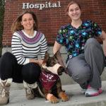 Emilia Terradas and McKenzie Dress on a sidewalk with Chief.