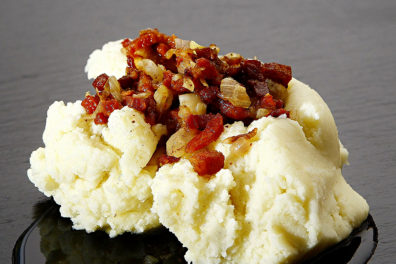 A closeup of mashed potatoes with bacon toppings.
