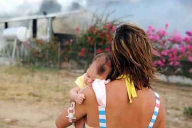 A young mother holding her sleeping baby as she watches their farm shed burn down.