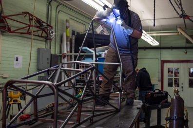 A student uses a welding tool on the Wazzu Racing team's car.