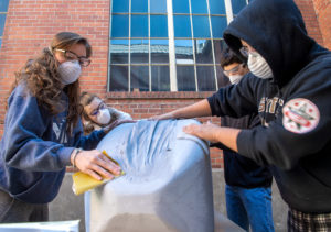 Neri Ganzarski and three other members of the Wazzu Racing Team sand away at one of the body panels of this year's race car.