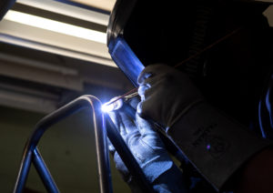 A student uses a welding tool to bring together the frame for the Wazzu Racing Team's car.