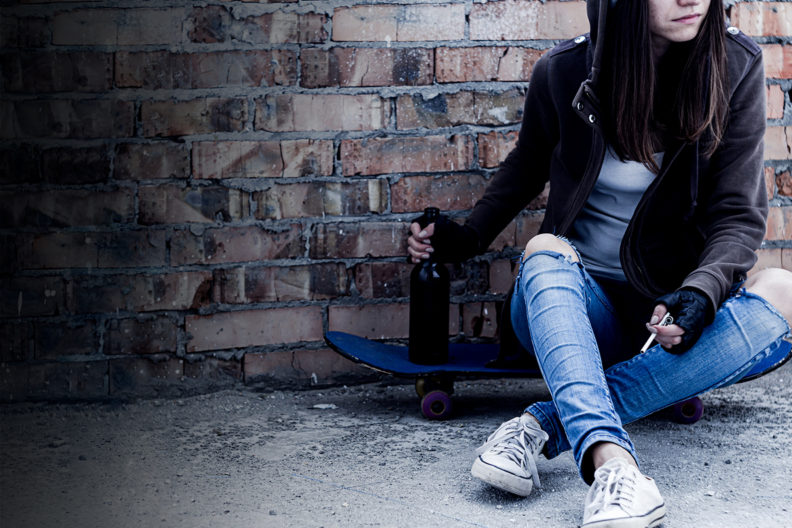 Teenage girl sitting outside smoking and holding a bottle of alcohol.