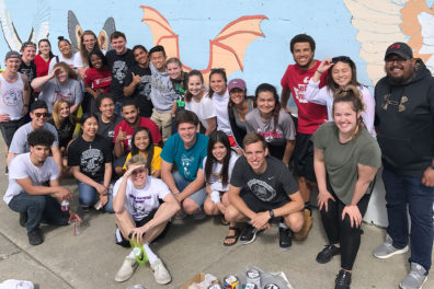 A large group of CCE student volunteers stand in front of an outdoor mural.