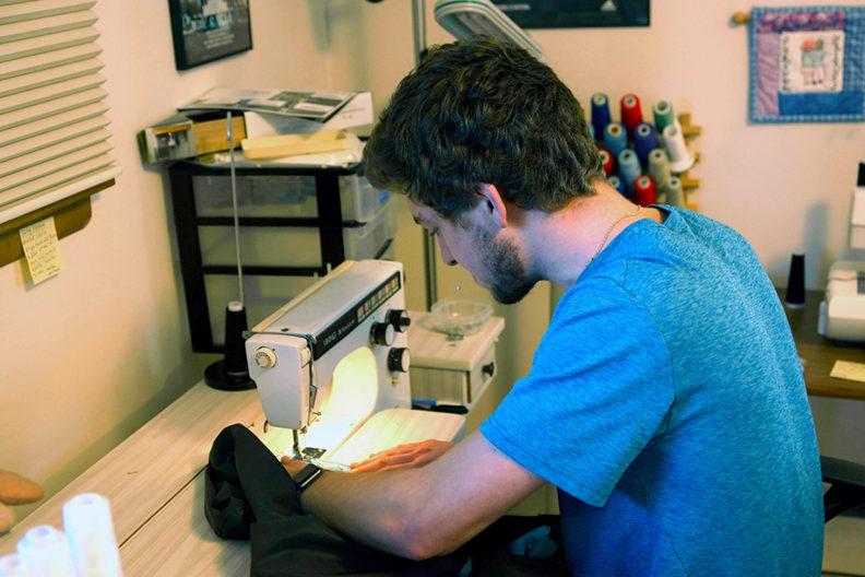 Closeup of Justin Janke using a sewing machine.