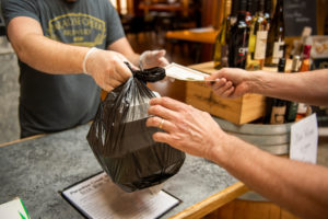 A customer picks up a take-out meal at Paradise Creek Brewery.