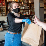 An employee at Black Cypress hands a free meal to a man.