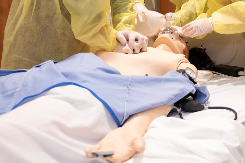Nurses practice on a simulation mannequin.