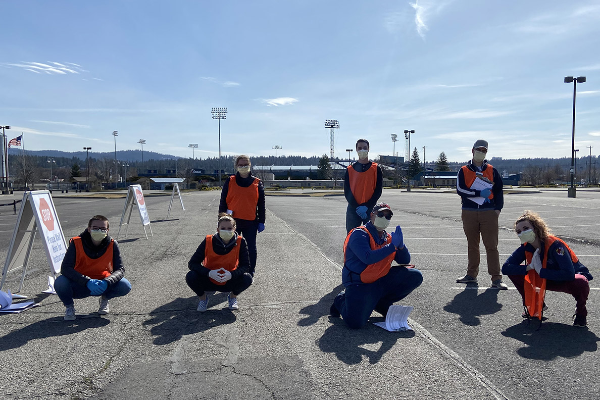 Students wearing medicla masks pose in parking lot of drive-thru testing site
