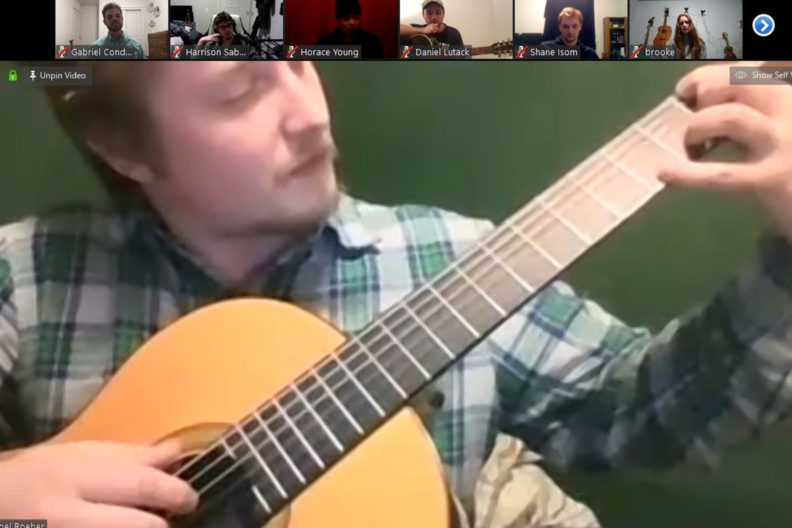 A man plays a guitar while people watch on Zoom.