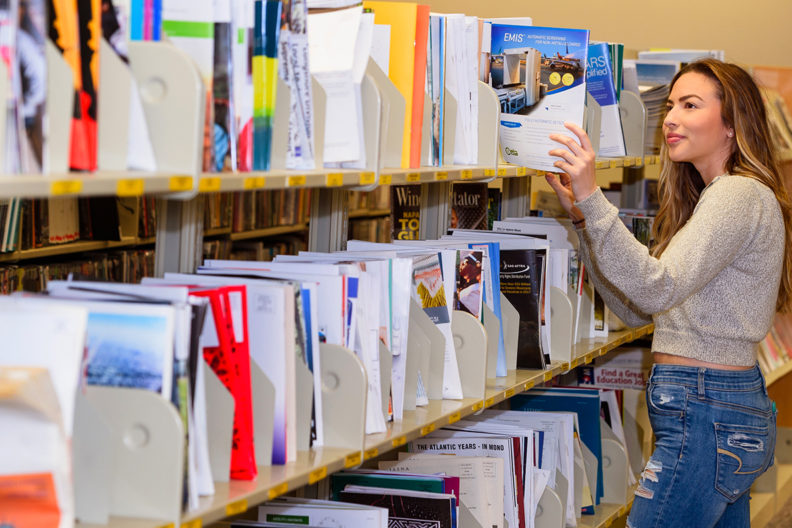 WSU student looking through stacks of journals in library.