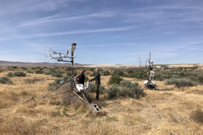 Two researchers standing by measuring equipment on an open stretch of scrubland