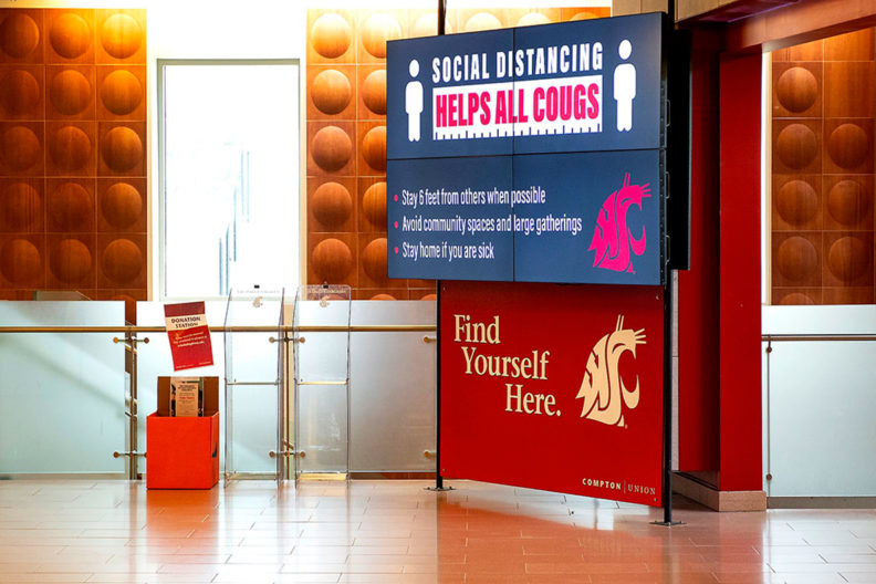Sign inside the CUB at WSU Pullman promoting social distancing.