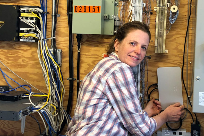 Carrie Backman checking on routers and other Wifi equipment.