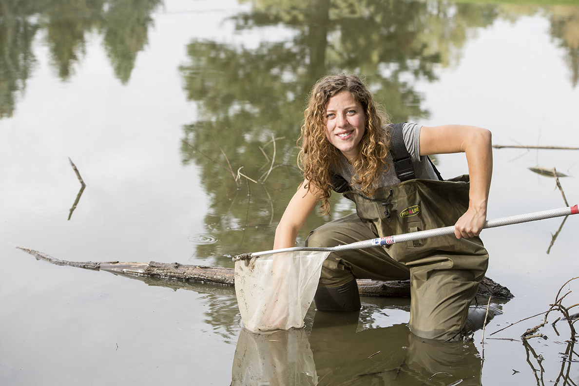 Emily Hall in a pond with waders and a net