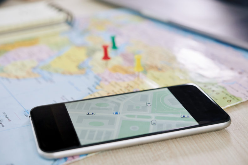A map with a smart phone placed on top of it.