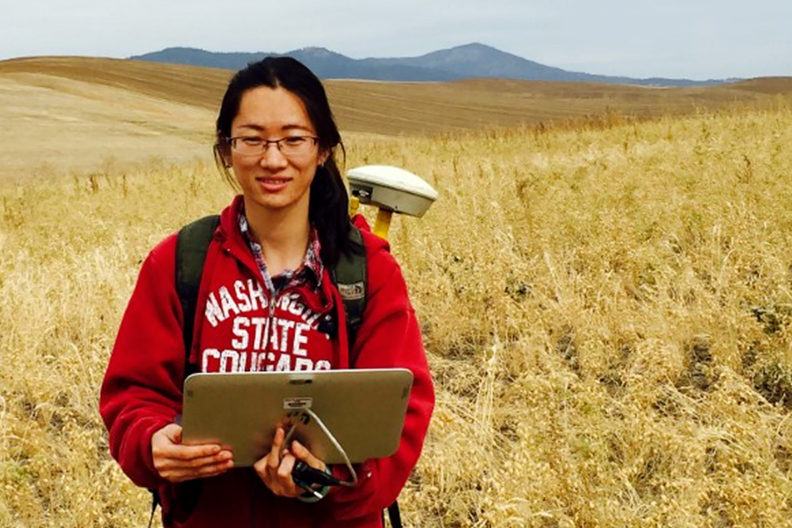 Closeup of Qiuping Peng standing in a field with a computer.