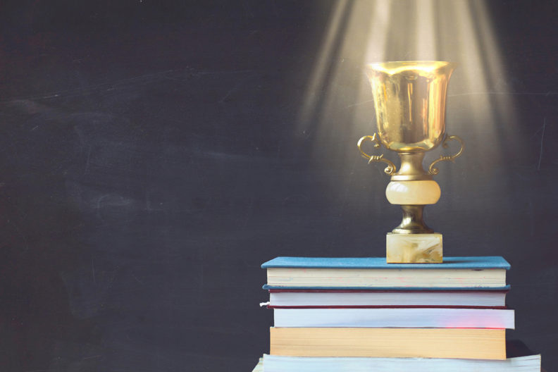 A shiny award resting on a stack of books.