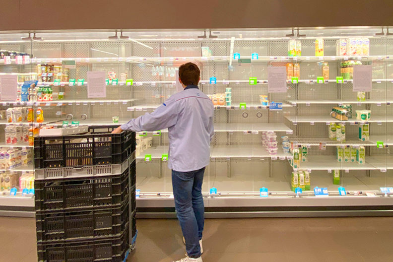 A grocery employee stands in front of several near-empty shelves.