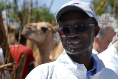 Closeup of Kariuki Njenga with a camel in the background