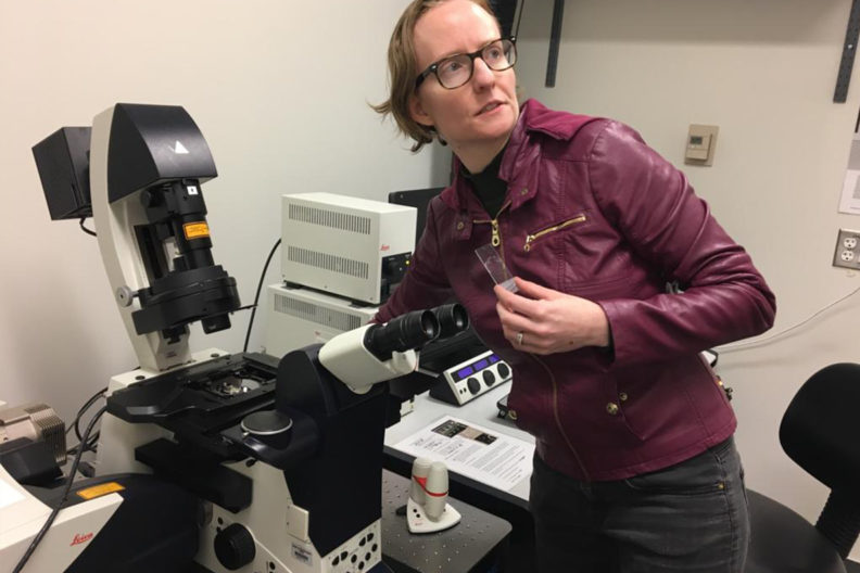Beverley Rabbitts stands next to an electron microscope holding a specimen slide.