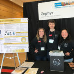 Three students stand behind their invention at a poster competition