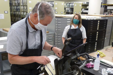 Two people work at a letterpress.
