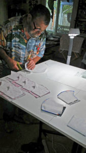 Frank Wallace uses templates to cut out the fabric for each mask.