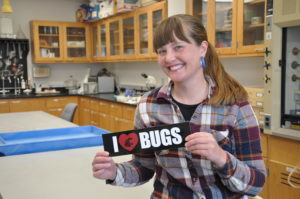 Megan Asche holding an I love bugs sign.